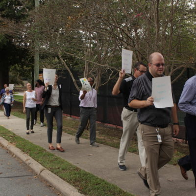 Principals carry their freedom signs as they march down Roberson St.